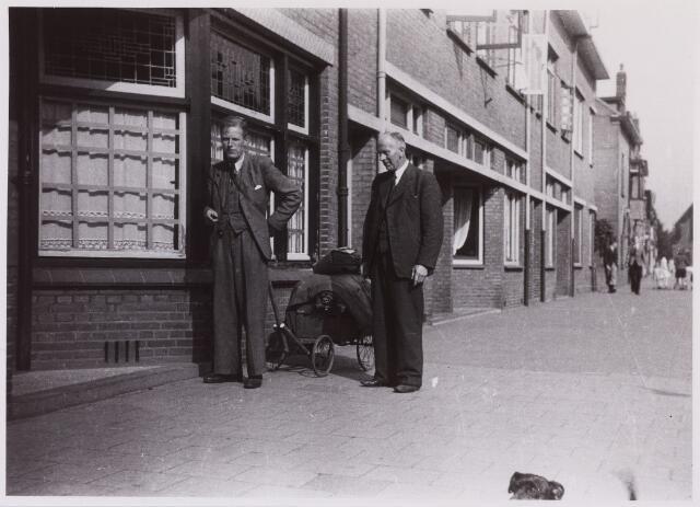 012247 - WO2 ; WOII ; Tweede Wereldoorlog. Bevrijding. Blokhoofd T. W. A. Borgertens, met gasmaker op de rug, en zijn schoonvader J. A. Holtrop voor de post aan de Nieuwe Bosscheweg, hier gefotografeerd na de bevrijding