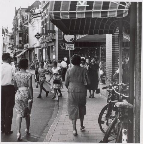 021612 - Winkelend publiek in de Heuvelstraat in 1959 ter hoogte van het pasverbouwde Vroom & Dreesmann, dat op 22 mei van dat jaar was heropend