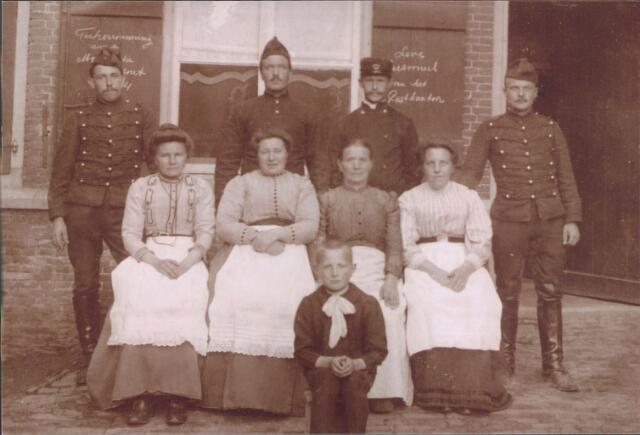 """650885 - Udenhout, postkantoor. De namen van de mensen op de voorgrond zijn helaas onbekend. Op de luiken achter hen staat rechts: """"Leve Personeel van het Postkantoor"""" en links """"Ter herinnering aan de Mobilisatie 1914"""" (deel van de tekst is obscured door de milicien die ervoor staat)."""