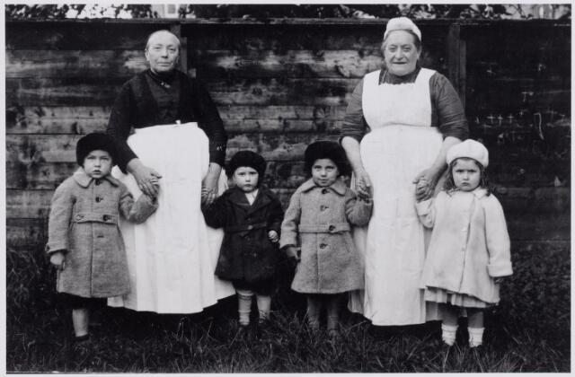 046078 - Van links naar rechts de kinderen Kees Trimbos, Jan Kerstens, Jan Trimbos en Ans van Besouw. De jongens waren kleinzonen van de Goirlese fabrikant Jan van Besouw. Ans van Besouw was een dochter uit diens tweede huwelijk met Jans Vromans. De vrouw links is Johanna (Han) van de Pol, geboren te Goirle op 22 maart 1868 en aldaar overleden in het St. Elisabethgesticht op 31 maart 1947, de vrouw rechts Maria Elisabeth (Bet) van de Pol, geboren te Goirle op 8 september 1871 en aldaar overleden op 31 juli 1927. Han en Bet waren zussen, dochters van Antonius van de Pol en Ida van Sleeuwen. Bet was dienstbode bij fabrikant Jan van Besouw, Han was meid bij diens broer, priester Jozef van Besouw in Zevenbergen. In 1927 keerde Han terug van Zevenbergen naar Goirle. Bet van de Pol draagt het zogenaamde 'Bossche mutske'.