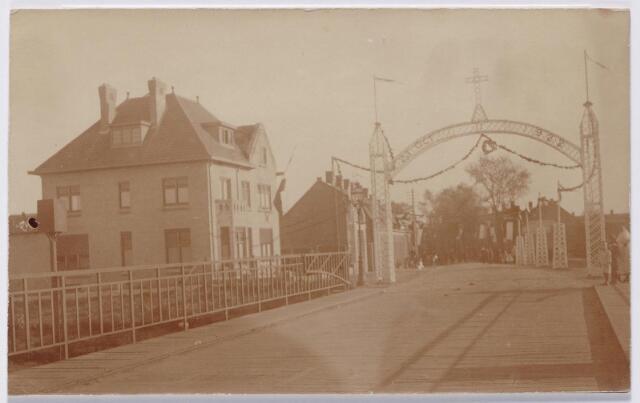 044495 - Ereboog aan de Hoevenseweg ter gelegenheid van de inwijding van de kerk van O.L.V. van Lourdes (Koningshoeven) door mgr. Diepen. Op de voorgrond de brug over het Wilhelminakanaal.