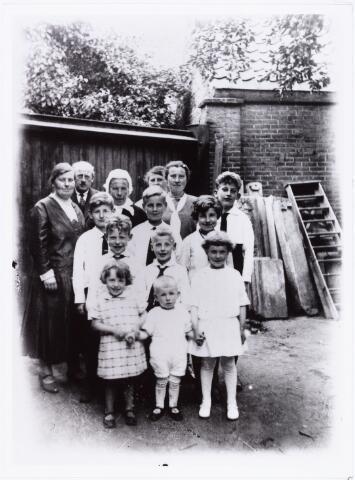 007468 - Foto gemaakt op de achterplaats van café de Boekanier in 1932. Op de laatste rij v.l.n.r. Trees Reijven en haar man Piet van Merendonk, haar moeder Reijven- Leemans, Adriana van Gorp- Reijven en de ongehuwd gebleven To Reijven. De vier kinderen op de voorlaatste rij zijn v.l.n.r. Toon van Merendonk, Frans van Merendonk, Wilhelmina en Sjaak van Gorp. Op de volgende rij v.l.n.r. Jan en Antoon van Gorp. Op de voorgrond Jo van Gorp en Kees en Wilhelmina van Merendonk.