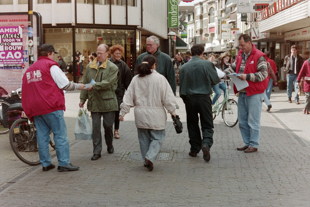 1237_001_044_019 - Staking van de CNV en FNV Bouw- en Houtbond voor een betere Bouw CAO in april 1995. Er worden folders uitgedeeld in een drukke Heuvelstraat.