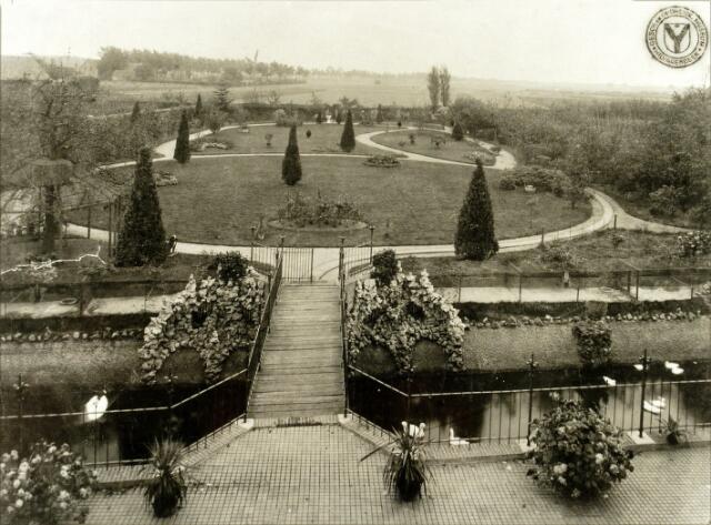 """054505 - De tuin van de pastorie aan de Koestraat tijdens het pastoraat van pastoor Jurgens. In de 18e eeuw werd in deze tijd, toen genaamd """"d'n dries van kannunik Van den Nieuwenhuijsen"""" de tweede schuurkerk van Hilvarenbeek gebouwd. Op de voorgrond de Zuiderbeek. Op de achtergrond links de Esbeekseweg met de Akkermolen."""