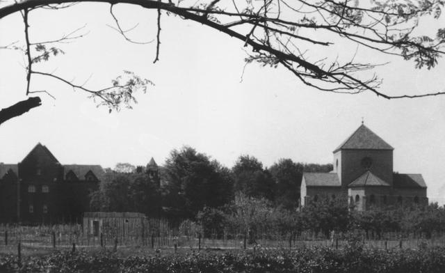 105202 - Links het oudste gedeelte van de Sint Paulusabdij, gebouwd tussen 1906 en 1910. Architect was Dom Paul Bellot, monnik van Solesmes. Het gastenverblijf kwam tot stand in 1938/1939. Toen de oude abdijkerk te klein was geworden, werd tussen 1953-1956 een nieuwe gebouwd,  het gebouw rechts, naar ontwerp van architect J.H. Sluijmer uit Enschede.. Op de voorgrond de nieuw aangeplante boomgaard. Kloosters. Sint Paulusabdij.