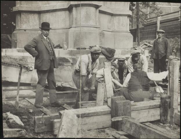 603676 - Verplaatsing van de gedenknaald van Willem II.  Het monument was 12,8 meter hoog, woog 90.000 kilo en besloeg een oppervlakte 25 vierkante meter. De verplaatsing geschiedde door de firma H. van Eijndhoven en Zonen uit Tilburg. Het monument werd geplaatst op ijzeren balken en rollen en met behulp van takels voortgesleept naar de nieuwe standplaats. Geheel links staat Hubertus C.P. van Eijndhoven (Tilburg 1877-1952), toezicht houdend op de werkzaamheden. De jongen in het midden tussen de arbeiders, half verscholen achter een opstaande plank, is de oudste zoon van aannemer van Eijndhoven, Marcel.