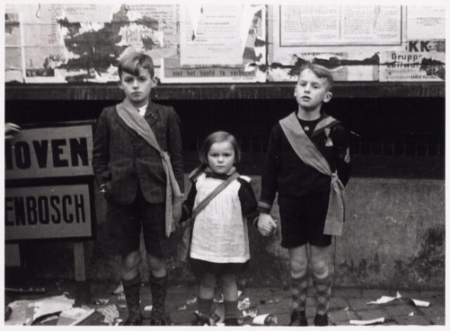 013305 - Tweede Wereldoorlog. Bevrijding. Drie kinderen van fotograaf Hendrikx uit de Zomerstraat (Piet, Wien en Marie-Louise), voorzien van een oranje sjerp, poserend voor het aanplakbord bij de boterhal naast het stadhuis op de Mark.
