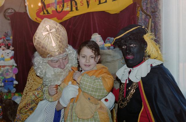 1237_001_003_011 - Feest. Korvel Winkelstraat. Sint Nicolaasviering. Een meisje poseert met Sinterklaas en Zwarte Piet tijdens een Sinterklaasfeest georganiseerd door winkeliersvereniging Korvel Vooruit op 27 november 1999.