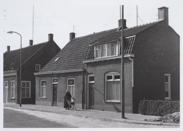 025648 - Panden Leharstraat 128 (links) en 130 (rechts). Vrouw in klederdracht achter een wandelwagen
