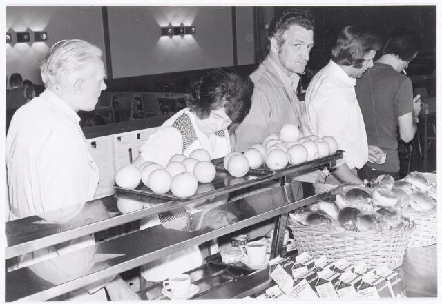 038679 - Volt. Noord. Bedrijfsrestaurants. De keuze in de kantines werd steeds groter. Hier in kantine gebouw NL waren in mei 1976 behalve broodjes ook sinaasappels, appels en voorverpakte melk te koop.  De 3e persoon van rechts is Dré Simons.