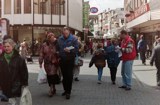 1237_001_044_020 - Staking van de CNV en FNV Bouw- en Houtbond voor een betere Bouw CAO in april 1995. Er worden folders uitgedeeld in een drukke Heuvelstraat.