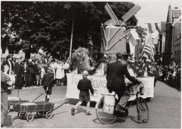 042782 - Tweede Wereldoorlog. Bevrijding. Een wagen met een molen en het opschrift 'Productieslag 1945' symboliseert de wil om het land weer op te gaan bouwen. Optocht tijdens de bevrijdingsfeesten.