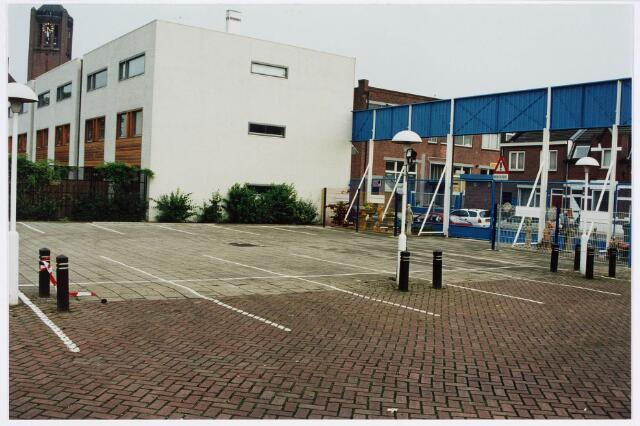 034122 - Voltstraat 43. Parkeerterrein van van Gorp Bolsius. Foto van rond 1998 in oostelijke richting. Linksboven de toren van de kerk van Broekhoven I aan de Broekhovenseweg.  Rechtsachter gebouw B van Volt waar boven de kantine en de gymzaal van gymnastiek ver. Volt was gevestigd. Sinds 2001 is hier de Ir.Kippermanstraat genoemd naar een vroegere (van 1930-1960) directeur van Volt.