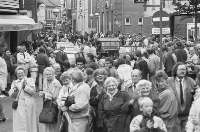 """TLB023000119_002 - Toeschouwers en militaire voertuigen uit de 2e Wereldoorlog tijdens een parade ter gelegenheid van de Bevrijdingsfeesten in 1989. Opname gemaakt op het in de volksmond genoemde """"Radiopleintje"""""""