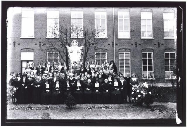 009370 - Kloosters. Het 100 jaar bestaan van de Zusters van O.L.V. Moeder van Barmhartigheid (Zusters van Liefde) aan de Oude Dijk. Groep oud weeskinderen.  Op de achtergrond het Heilig-Hartbeeld.
