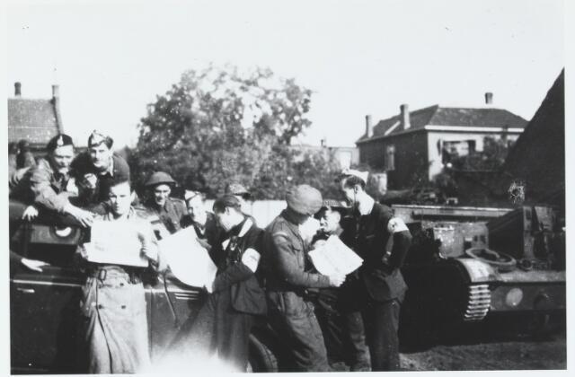 055638 - WOII; WO2; Hilvarenbeek, bevrijding. Engelse bevrijders te Hilvarenbeek in 1944. Zij lezen het bevrijdingsnummer van de Hilverbode.