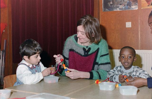 1237_001_038_025 - Vrijwilligerswerk. Een vrijwilliger van stichting Contour helpt kinderen bij het maken van een kralenketting in maart 1998.