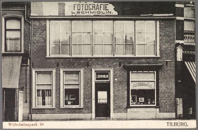 011039 - Louis Schmidlin, geboren te Haarlem op 30 januari 1870 begon op 11 juli 1908 zijn fotozaak in het pand Gasthuisstraat K540a, vanaf 1910 Gasthuisstraat 32. Weldra was hij niet alleen bekend als portretfotograaf, maar ook als fotograaf van activiteiten zowel in als buiten Tilburg. Zo maakte hij in 1909 een foto van de aanbieding van een kinderwagen aan koningin Wilhelmina door de provincie Zeeland. Zijn activiteiten als fotograaf in Tilburg begon hij met een fototentoonstelling bij boekhandel Gianotten. Op 21 januari 1917 verplaatste hij zijn zaak naar het pand Wilhelminapark 39, waar hij ook een lijstenhandel begon. In 1925 werd een filiaal in Dongen geopend. Louis Schmidlin werd als fotograaf opgevolgd door zijn zoon Louis Albert Schmidlin. Het vijftigjarig bestaan van de firma is in 1958 gevierd met een drukbezochte receptie waar volgens de krant 'moederke Schmidlin' (Johanna Roselina Dubois geboren te Maastricht op 21 april 1874) vele bekenden terugzag uit de fotowereld.