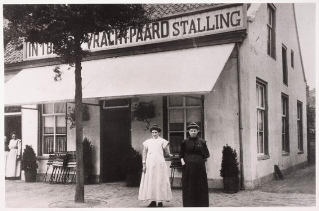 """033359 - Café 'In 't Bruine Vrachtpaard' aan de Bosscheweg 232, eigendom van Nicolaas Martinus (Tinus) van Iersel, bijgenaamd """"boerke Van Iersel"""". Hij werd geboren te Berkel in 1877 en was voor zijn huwelijk arbeider van beroep. In 1904 trouwde hij met Martina Henrica (Stiena) Verhoeven, die in 1879 in Tilburg geboren werd. Vanaf 1904 staat Van Iersel vermeld als caféhouder. In 1934 verhuisde het echtpaar naar de Lanciersstraat. Stiena van Iersel-Verhoeven staat rechts op de voorgrond, links haar dienstbode Huijbregts. Vanaf 1932 droeg dit pand het huisnummer Bosscheweg 518. Later zat er het 'Motorhuis' van Toon Hoes. Rond 1960 is dit pand gesloopt."""