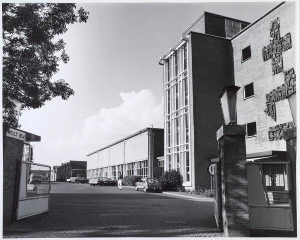 019897 - Fabriekspoort en kantoor van Volt in de Groenstraat. Na de sluiting werden in de gebouwen verscheidene kleinschalige bedrijven gehuisvest. Het kantoor rechts bood onderdak aan de Academie voor Journalistiek en Voorlichting. Het kunstwerk aan de gevel werd gemaakt door Jacques van Rhijn.