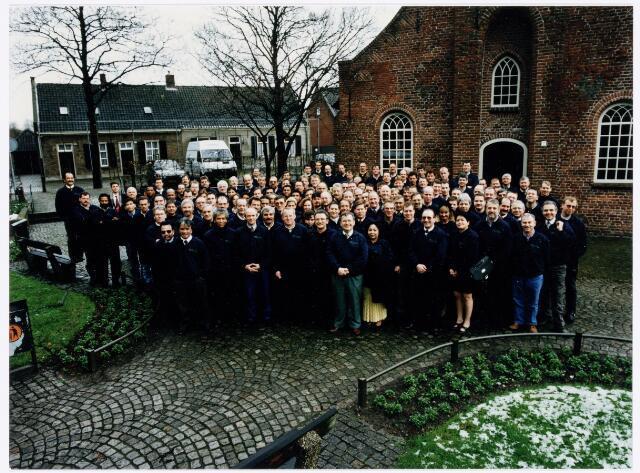038962 - Volt. Noord. In januari 1995 werd K.M.T. overgenomen door het Japanse bedrijf J.S.T. Vandaar deze foto van het nagenoeg voltallige personeel voor de Hasseltse kapel. Echter na enkele weken werd de overeenkomst alsnog afgeblazen. Een latere overname in het jaar 2000 door Key Tec bood ook nauwelijks perspectief. In 2001 werd de productie overgeplaatst naar de Key Tec vestiging in Eindhoven. Daarmee kwam voor Tilburg een einde aan de historie daterend van 1928 toen met de overgang van de productie van gloeilampen naar radio onderdelen de productie of fabricage afdeling metaalwaren werd opgericht. K.M.T was in feite een voortzetting van die afdeling.