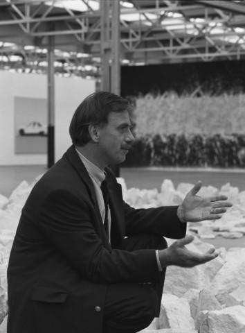 TLB023000933_001 - Kunst en cultuur. Hendrik Driessen, tot 2019 directeur van museum De Pont. Zittend bij een stenen cirkel het werk Planet Circle van kunstenaar Richard Long.