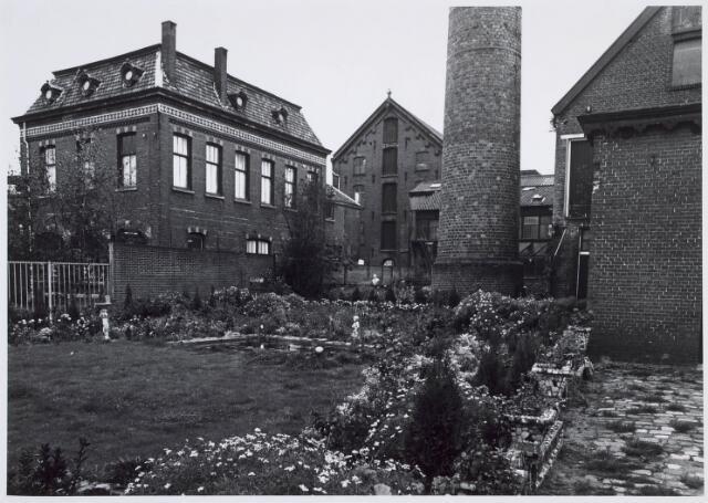 019222 - Tuintje op het complex van wollenstoffenfabriek C. Mommers. Het vierkante gebouw links was het kantoor. Midden op de achtergrond staat het hoogste fabrieksgebouw dat ooit in Tilburg is gebouwd. Het is in twee etappen tot stand gekomen, te weten in 1885 en 1894. Thans behoort het tot het Nederlands Textielmuseum