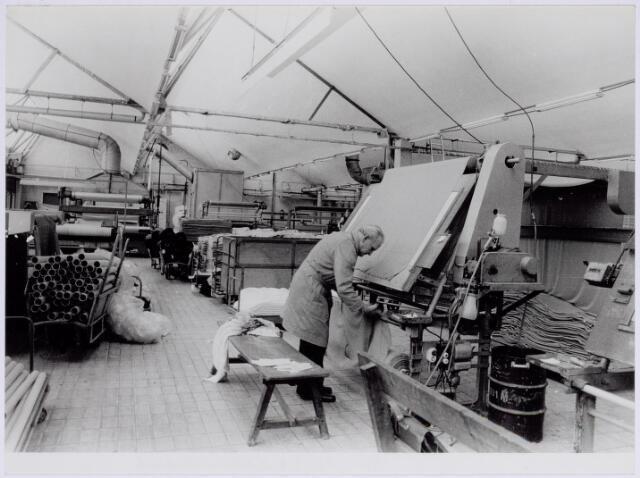 037949 - Textiel. Stukkencontroleur bij wollenstoffenfabriek George Dröge. De stof hing voor een lichtbak, waardoor oneffenheden en weeffouten duidelijk zichtbaar werden. Deze werden aangestreept en in de stopperij hersteld
