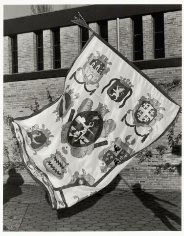 067351 - Schuttersgilden. Handboogschuttersgilde Sint Sebastiaan. Vaandel van het gilde Sint Sebastiaan, hier gebruikt b.g.v. de priesterwijding en eerste H.Mis van Theo van Dun in de parochiekerk van Petrus en Paulus aan de Vierwindenlaan. Het vaandel is een op onderdelen gewijzigde kopie uit 1968 van een grotendeels verloren gegaan exemplaar uit tenminste de 19e eeuw.  n het medaillon is de patroonheilige afgebeeld. Daaromheen vanaf linksboven met de klook mee; het gemeentewapen van Tilburg, het wapen va de Staten Generaal der Verenigde Nederlanden; het wapen van Jerusalem (symbool Sebastiaan als  patroon van de kruisridders); het familiewapen Schetz van Grobbendonck, heren van Tilburg, het familiewapen Van Dun (Cees van Dun was de eerste hoofdman van het gilde na de heroprichting in 1967); het familiewapen Van Haestrecht, heren van Tilburg; het familiewapen Becht (burgemeester C. Becht was 'gildeheer'); het familiewapen Van Malsen, heren van Tilburg.