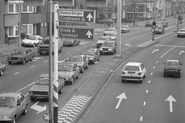 TLB023000018_001 - Autoverkeer, stoplichten en verkeersborden ter hoogte van de Sacramentskerk. Foto gemaakt ten behoeve van de Begrotingskrant van Tilburg, waarin wordt aangegeven dat de stad financieel gezond is als gevolg van het Tilburgs Model