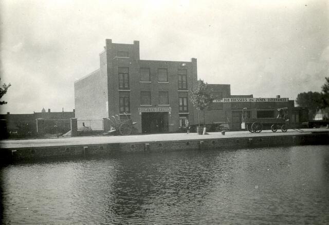 082721 - Graan- en Meelhandel H. Schraven-Eijsbouts,  Op 10 mei 1924 werd door oudste dochter Catharina (Toos) Schraven, de eerst steen gelegd van dit uit gewapend beton opgetrokken magazijn. Het was gebouwd naar ontwerp van de Tilburgse architect Van Poppel. Deze foto van het gebouw aan de Piushaven is van 8 augustus 1929: de uitbreiding van het gebouw dat in 1924 als eerste is gebouwd  (zie fotono. 082722)