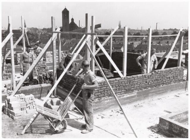 039177 - Volt. Zuid. Nieuwbouw, Gebouwen. De bouw van het nieuwe Hoofdkantoor aan de Groenstraat in 1960.  Op de achtergrond de kerken v.l.n.r.: Heike, Broekhoven I, en de Heuvel. Opmerkelijk is het toen nog grote aantal fabrieksschoorstenen.