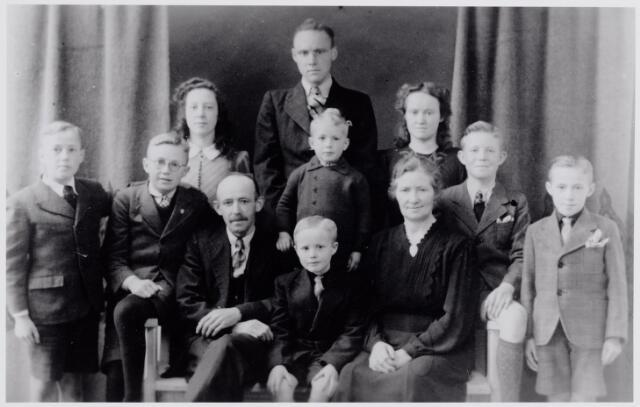 046003 - De familie Van Gils-de Rooij. Op de eerste rij v.l.n.r. Ben van Gils, geboren te Goirle op 25 augustus 1931, Jan van Gils, geboren te Goirle op 12 juli 1928, Nicolaas (Klaaske) van Gils, geboren te Goirle op 17 februari 1895, Wies van Gils, geboren te Goirle op 21 mei 1936, Nel de Rooij, geboren te Goirle op 24 decenber 1896, Toon van Gils, geboren te Goirle op 24 januari 1930 en Wil van Gils, geboren te Goirle op 22 november 1934. Op de tweede rij v.l.n.r. Toos van Gils, geboren te Goirle op 19 oktober 1926, Pierre van Gils, geboren te Goirle op 11 februari 1923, voor hem Ger van Gils, geboren te Goirle op 21 juni 1939 en Bets van Gils, geboren te Goirle op 19 maart 1925.