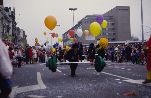 656872 - Carnaval Tilburg. Carnavalsoptocht in 1987.  Gewichtheffen. Loopgroep tijdens d'n Opstoet.  Met op de achtergrond het oude postkantoor.