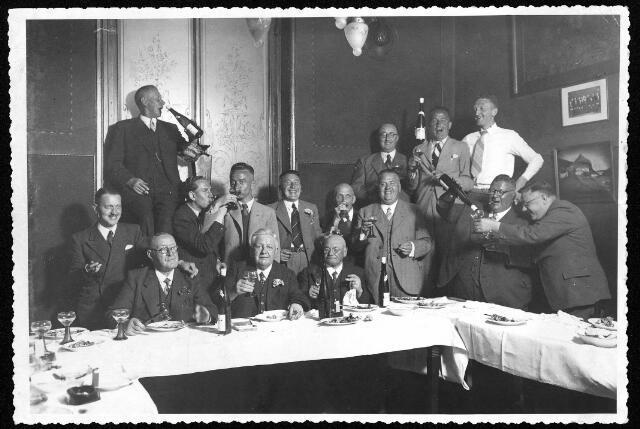 """064603 - Gezelschap in café Oud-Holland, """"Dispuut de X""""  aan het Piusplein. Aan tafel in het midden met twee glaasjes in zijn hand: Joannes Jacobus Willems, geboren te Tilburg op 11 augustus 1878 en aldaar overleden op 22 mei 1945. Hij was juwelier aan de Heuvelstraat 42a en getrouwd met H.M.J. Lammers. De dikke man tweede van rechts, met fles in zijn hand is Jules Pessers. Hij was vertegenwoordiger bij autobedrijf Knegtel. Pessers, geboren te Tilburg op 4 juli 1898 en aldaar overleden op 19 februari 1968, was ongehuwd en woonde met zijn moeder en zus Maria in de Telefoonstraat. schuin rechts achter de voornoemde Willems, met bloem in het knoopsgat, Otto Höhner sr. directeur van een vilt- en lederfabriek aan de Koestraat."""