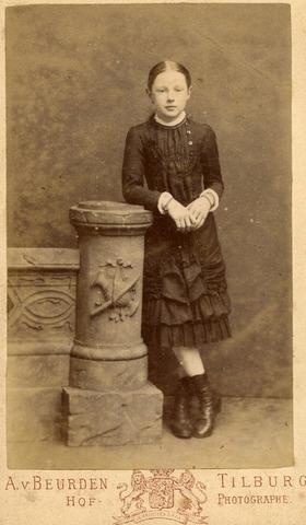 602733 - Onbekend meisje in het atelier van fotograaf Adriaan van Beurden (1843-1915). Het versierde ornament is een typisch modeverschijnsel uit deze periode.