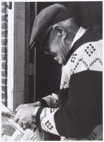 016756 - Bewoner van het pand Buitenstraat 5 J.H. Speijers leest een krant in de deuropening