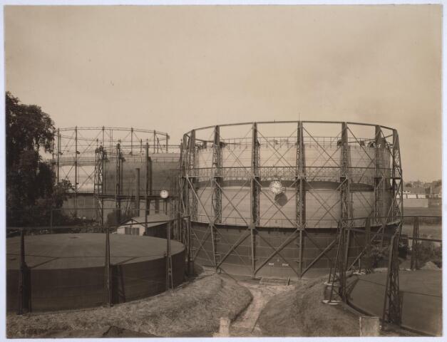 025175 - Gashouders van de gemeentelijke gasfabriek. Hierin werd een buffervoorraad gas opgeslagen