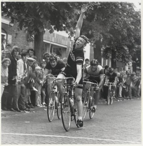 90936 - Made en Drimmelen. Marcel Pennings wint  in 1970 de Ronde van Made. Marcel Pennings reed voor de wielerploeg Vredestein en was ook lid van wielerclub De Bataaf in Halfweg. Op de achtergrond de bakkerij van C. van Dongen in de Marktstraat in Made.