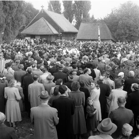 050339 - Bedevaartgangers op de geboortegrond van Peerke Donders aan de Pater Dondersstraat. Links de kapel, rechts het gereconstrueerde geboortehuis. De bedevaartgangers luisteren naar een preek van redemptorist pater De Witte.