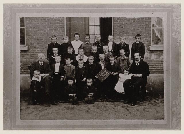 100167 - Onderwijs. Basisschool. Klassenfoto van de jongensschool. Torenstraat 4. Links zit meester Kunst, zijn driejarig zoontje Hubertus staat bij hem. Helemaal rechts zit meester Durlinger met dochtertje Huberta. Pietje Smits, 9 jaar, mag het bordje vasthouden