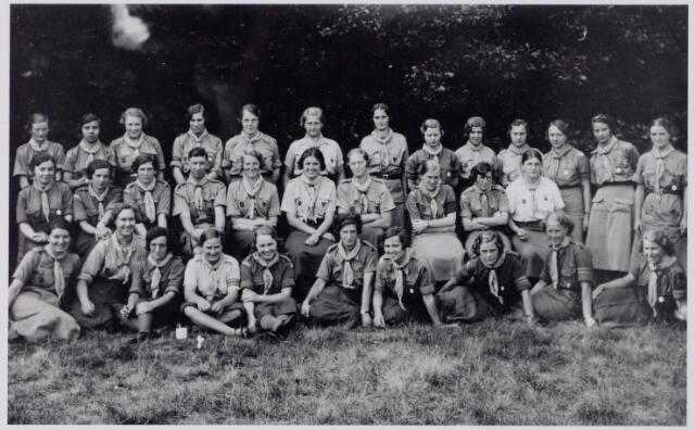 """044282 - Groep welpenleidsters en een verkennersleider. Ze dragen allen de """"woodbadge"""", dat is een das met lederen koord in kralen. De das was grijs, roodachtig gevoerd, met achterop een blokje van blauwe Schotse ruit. Deze onderscheiding werd door lord Baden Powell alleen uitgereikt aan deelnemers aan de zogenaamde """"Ommencursus"""". Tilburg telde maar enkele """"woodbadge""""-draagsters. Een van hen was Mien van den Dries (mogelijke staande vierde van rechts). Zij was """"commissaresse"""" van de welpen in het district (toen adjunctenaat) Tilburg. Rechts dragen de vrouwen op het borstzakje een insigne met kruis, wat betekent dat dit een katholieke groep is."""