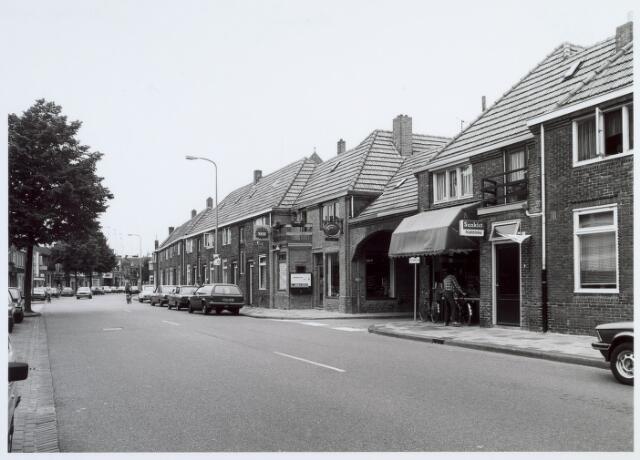 016634 - Broekhovenseweg in de richting van het centrum. Onder het poortje de Van Malsenhof, met links daarvan een tabakswinkel en rechts een groentehandel