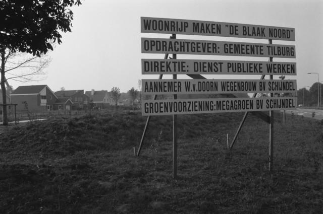 """TLB023000475_001 - Kennisgevingsbord voor het woonrijp maken van """"De Blaak Noord"""" in opdracht van de Gemeente Tilburg onder Direktie van Dienst Publieke Werken. De huizen op de foto zijn gelegen aan  de Grevelingen."""