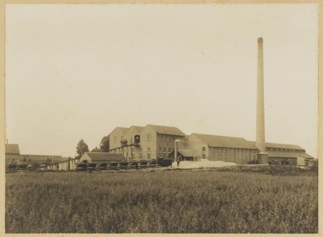 068563 - Achterzijde steenfabriek Stevens aan de Lovense Kanaaldijk hoek Enschotsestraat, de huidige Kapitein Nemostraat. Het bedrijf startte in 1920 en was destijds met zijn droogkamers de modernste van Nederland. De leem werd na droging - wat gebeurde met afvoerwarmte van de steenoven - als vormbaksteen in de ringoven gereden en op een temperatuur van 1050 graden Celsius gebakken. Als brandstof werd anthraciet (vetkolen) gebruikt. De produktie bedroeg 9 miljoen stuks in Waalformaat per jaar. Op de voorgrond is duidelijk de locomotief met de met leem gevulde kipkarren te zien, welke via een smalspoor over een afstand van wel twee kilometer van de fabriek af gelegen leemputten werden aangevoerd. Met de schop werd door zogenoemde 'leemstekers' tot op twee meter diepte afgegraven. In 1964 werd de grond waarop het bedrijfscomplex stond door de gemeente onteigend ten behoeve van de aanleg van Industrieterrein Loven. De foto is genomen vanaf de Nieuw-Lovenstraat (gedeeltelijk nog aanwezig als Nautilusstraat). De fotograaf stond ongeveer op de plaats waar nu de Gelrebaan loopt.