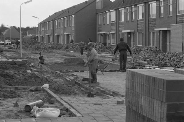 """TLB023000130_003 - Bestraters bezig met het aanbrengen van de bestrating in nieuwe woonwijk. Foto gemaakt in kader Reeshof """"gezond beleid"""""""