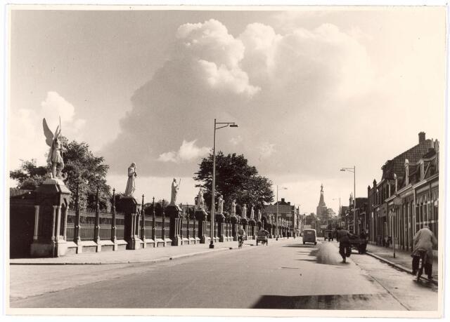 016044 - Bredaseweg in de richting van het centrum, met links het kerkhof en op de achtergrond de toren van de Heikese kerk