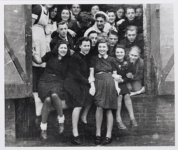 012294 - Tweede Wereldoorlog. Bevrijding. Vrouwelijke evacués uit de Betuwe, tijdelijk ondergebracht bij de schoenfabriek van Van Arendonk in de Nieuwstraat