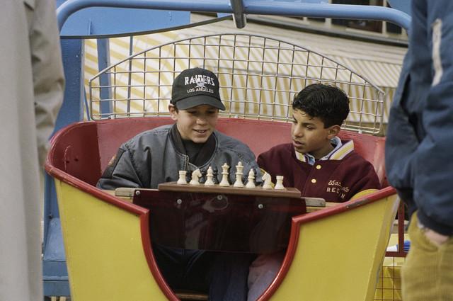"""TLB023000392_001 - Kinderen spelen in een gondel van een mini-rad een partij schaak, tijdens """"Tilburg Schaakt"""", welk toernooi parallel liep aan het Interpolis Schaaktoernooi."""