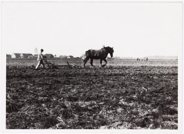 008560 - Ploegende boer met op de achtergrond een rij huizen en in de verte een groepje toekijkende mensen. gefotografeerd door Henri Berssenbrugge (1873-1959), begin 1900.